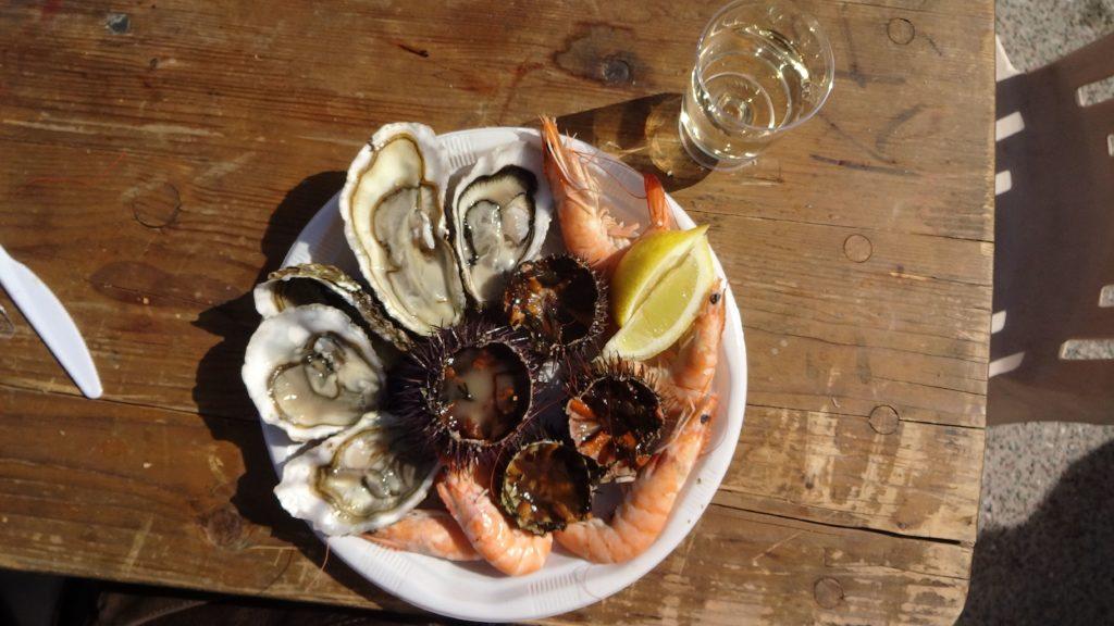 assiette de fruits de mer accompagné de son petit verre de vin blanc