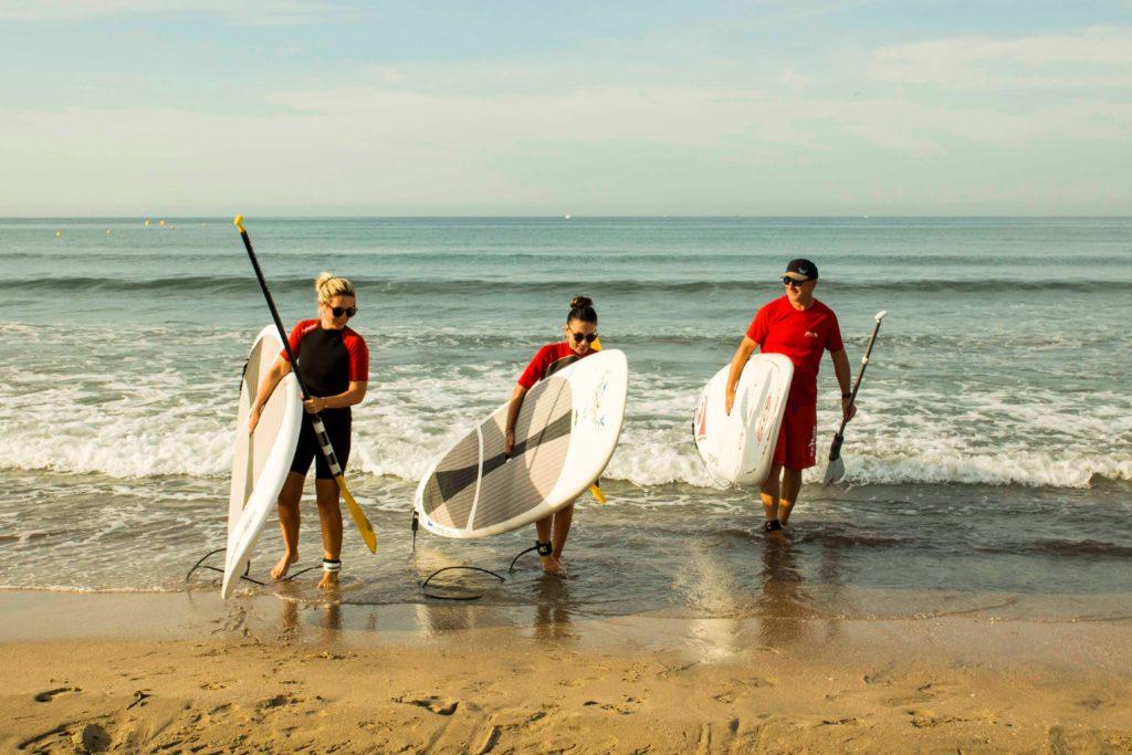 Le professeur et les élèves sortant de l'eau avec le paddle à la main
